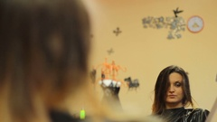 Girl looking in the mirror while her hairdresser hairdo Stock Footage