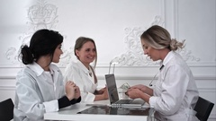 Female doctor pays the money to the nurses in office Stock Footage