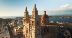 Aerial shot flying away from a church in Mellieha Malta Stock Footage