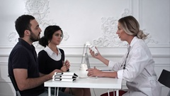 Female doctor sells the pills to family couple in the office Stock Footage