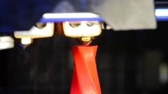 Automatic three dimensional 3D printer printing a bright red model close-up. Stock Footage