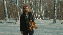 Happy man is wearing warm black coat in park with maple yellow leaves, winter Stock Footage