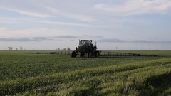 Tractor with high wheels is making fertilizer on young wheat. Stock Footage