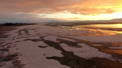 Aerial view of frozen landscape covered in snow during colorful sunset Stock Footage