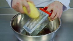 Cook rubs the potato on a grater Stock Footage