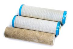 Dirty water filter cartridges on white background Stock Photos