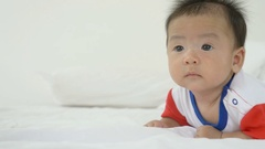 4K : Crawling pretty Asian baby boy on the bed, Pan shot Stock Footage