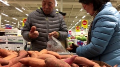 Motion of people selecting yam inside superstore produce department Stock Footage