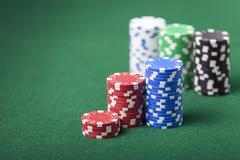 Stacked poker chips on green felt table. Shallow depth of field with focus .. Stock Photos