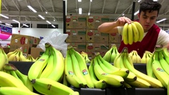 Motion of clerk stocking banana on display rack inside superstore Stock Footage
