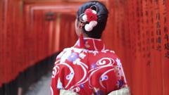 Japanese women in Red kimono walking at Famous Inari Orange temple gat Stock Footage