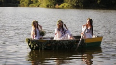 Three girls in the Slavic national costume in a boat floating on the river Stock Footage