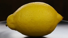 Yellow lemon turning on itself on a black plate background. Stock Footage
