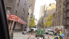 Driving past construction site digger tractor workers hardhats Manhattan NYC Stock Footage