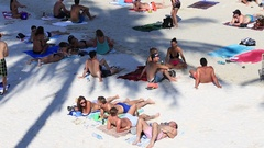 Girls and boys resting the beach before Full Moon party . Koh Phangan , Thailand Stock Footage