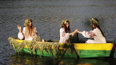 Three beautiful girls in the Slavic clothes in a boat floating on the river. Two Stock Footage