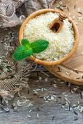 Bowl of white long grain rice on the old sacking. Stock Photos