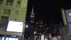 Empire State Building tilting 34th Street winter night people Manhattan 4K NYC Stock Footage