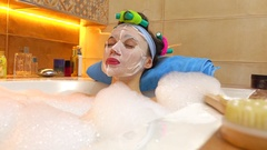 Beautiful young woman wearing cosmetic face mask relaxes in foamy bathtub Stock Footage