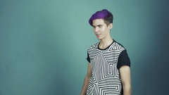 Young pleased blogger with purple hair talking something in web studio gray Stock Footage