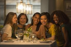 Portrait smiling women friends dining at restaurant table Stock Photos