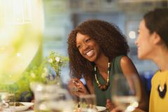 Women friends laughing and dining at restaurant table Stock Photos
