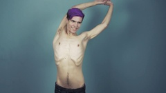 Young topless man with purple bangs posing in studio on gray background Stock Footage