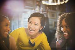 Smiling women laughing and talking in restaurant Stock Photos