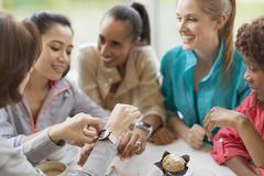 Smiling women friends looking at smart watches in cafe Stock Photos