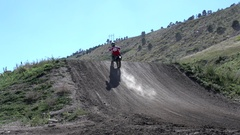 A young man riding his motocross dirt motorcycle off jumps. Stock Footage