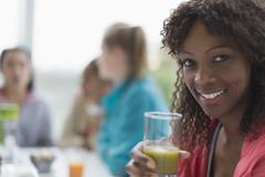 Portrait smiling woman drinking healthy green smoothie at cafe with friends Stock Photos
