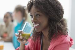 Smiling woman drinking healthy green smoothie in cafe post workout Stock Photos