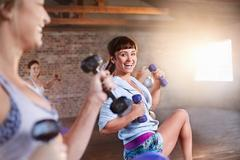 Smiling young women with dumbbells in exercise class gym studio Stock Photos