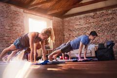 Exercise class practicing plank pose in gym studio Stock Photos
