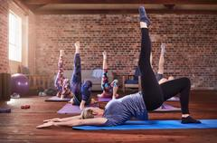 Fitness instructor and exercise class practicing one-legged bridge pose in gym Stock Photos