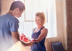 Trainer helping young female boxer putting on boxing gloves in studio Stock Photos