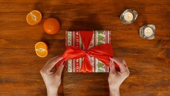 Girl is opening birthday gift box with red ribbon, top view Stock Footage