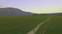 One person is on a road in the middle of an immense valley. About solitude Stock Footage
