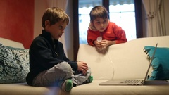 Kids watching internet media content in front of laptop computer screen Stock Footage