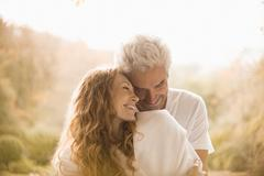 Affectionate couple hugging and smiling Stock Photos