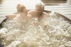 Smiling couple drinking champagne soaking in hot tub on patio Stock Photos