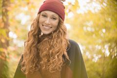 Portrait smiling woman in stocking cap under autumn trees Stock Photos