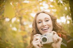 Portrait enthusiastic woman with digital camera under autumn trees Stock Photos