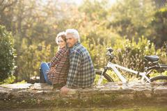 Portrait affectionate couple with bicycle resting on stone wall in autumn park Stock Photos