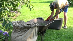 Landscaper worker man stop mower and unload grass from lawn cutter bag into Stock Footage
