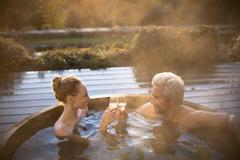 Couple toasting champagne glasses soaking in hot tub on autumn patio Stock Photos
