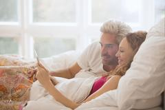 Couple relaxing laying in bed using digital tablet Stock Photos