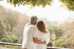 Affectionate couple hugging looking at autumn trees on patio Stock Photos
