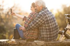 Affectionate couple hugging taking selfie with camera phone in autumn park Stock Photos