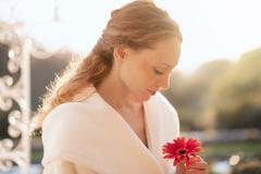 Serene woman holding red gerbera daisy on sunny patio Stock Photos